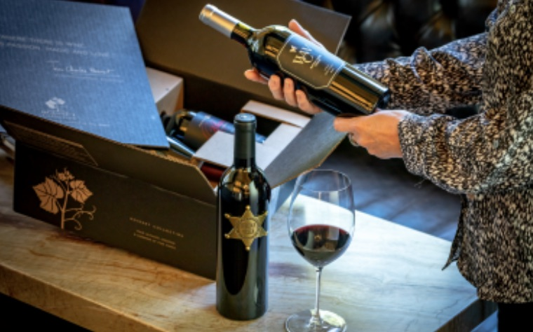 Photo of a woman holding wine she received from a customizable wine club, the Boisset Wine Society curated by Peggy and Brian Dean. Great value on winery direct selections.